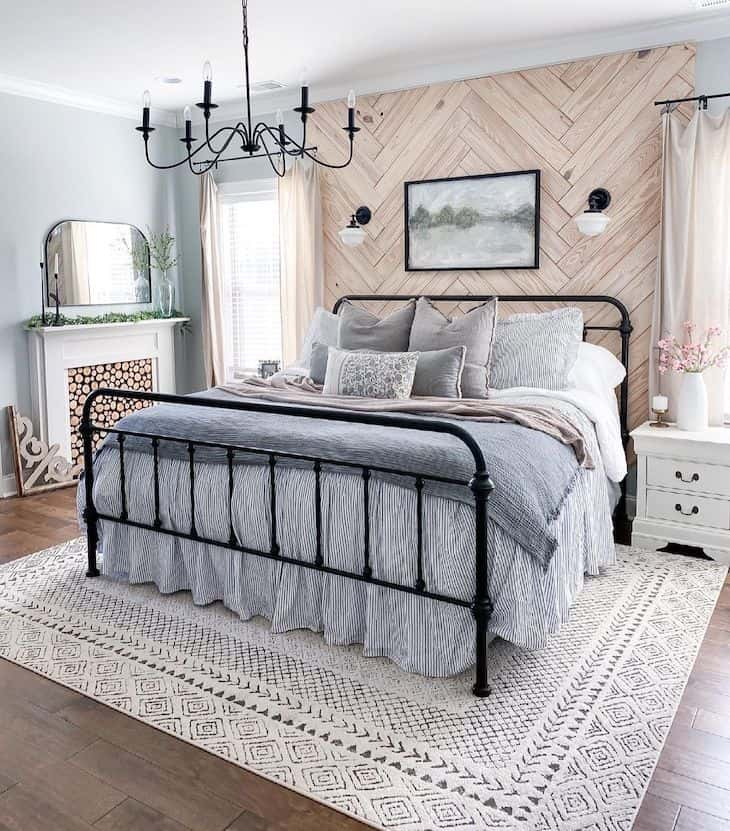 Herringbone shiplap accent wall in a bedroom with metal bed and windows on each side of the bed