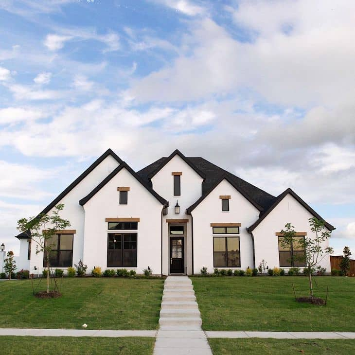 Blank and white modern farmhouse exterior with white brick, black door and black window trim
