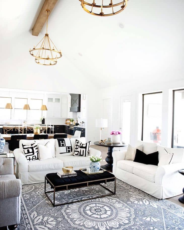 Open concept living room with white couches grey rug and upholstered coffee table