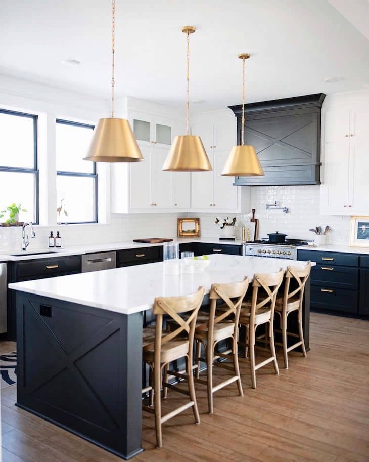 Black kitchen island with wood counter stools and brass kitchen lighting