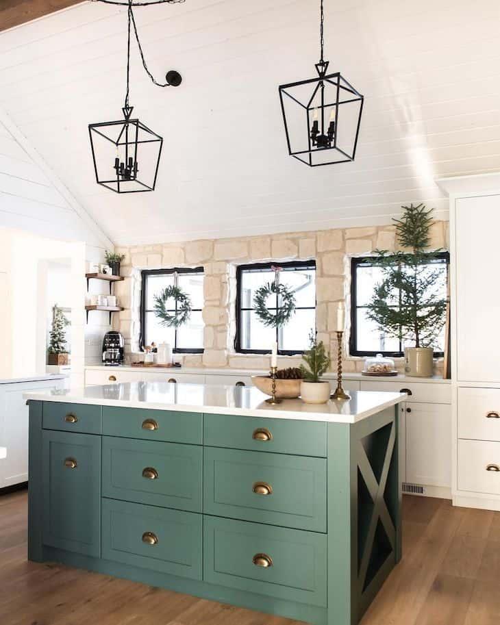 White kitchen with green island and natural stone backsplash