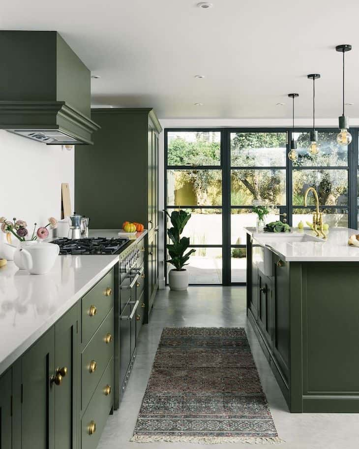 Olive green kitchen with polished concrete floor and bohemian rug