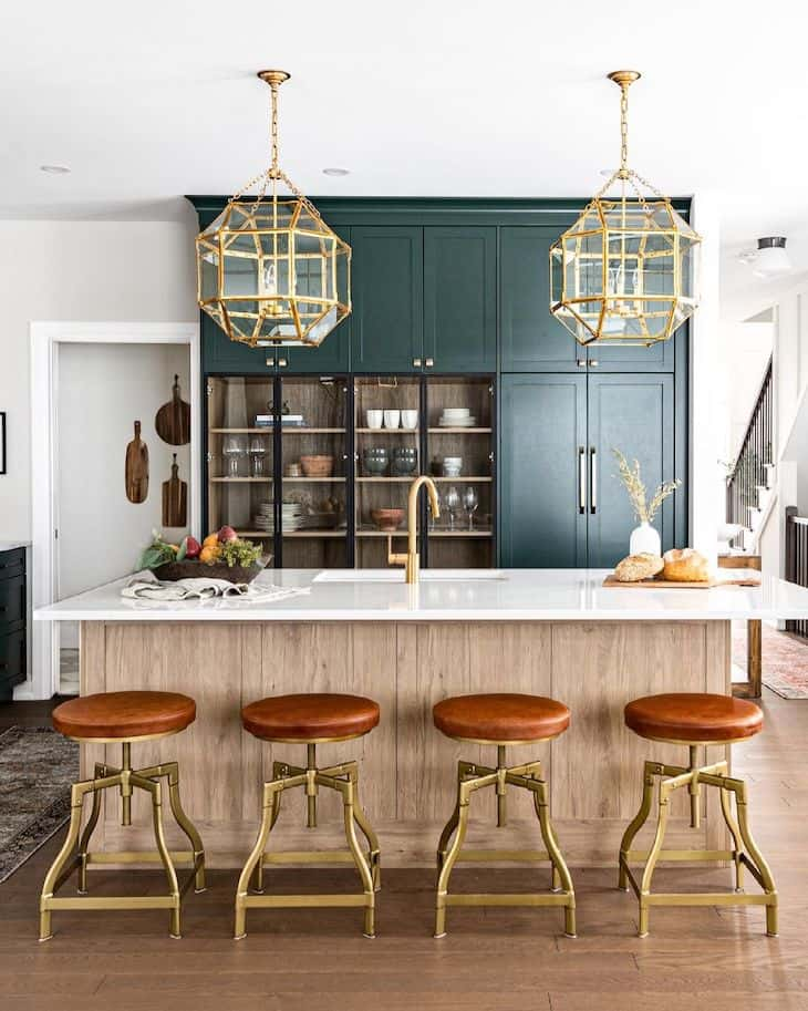 Green kitchen in color Essex Green by Benjamin Moore, with oak Island, antique brass bar stools and gold lantern pendants