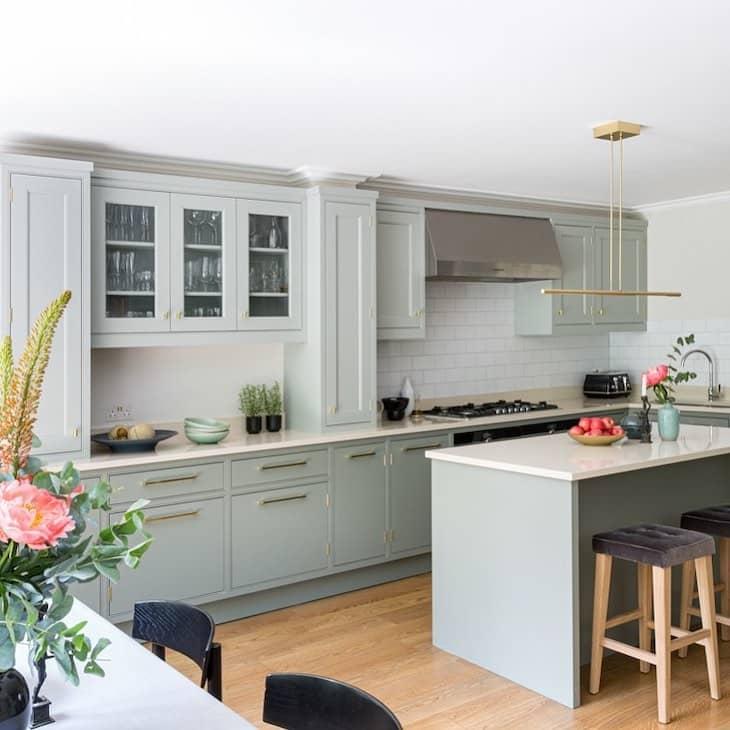 Sage green kitchen with glass upper cabinets and white subway tile backsplash