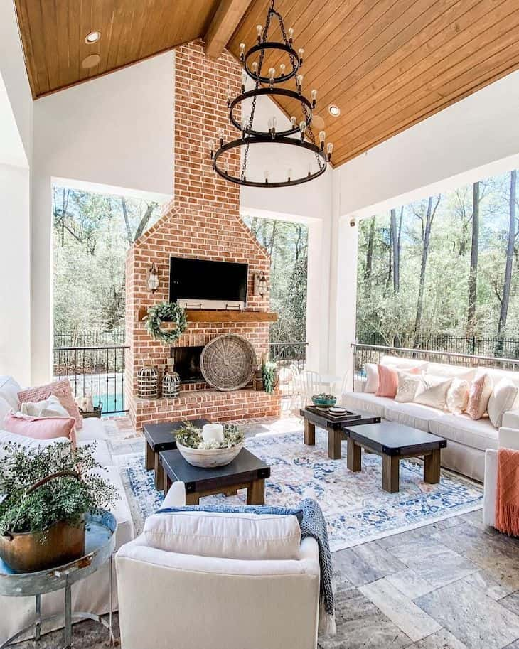 Covered outdoor patio with a brick fireplace