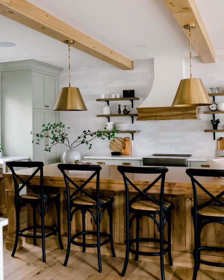 Black bar stools on wood kitchen island and sage green kitchen cabinets