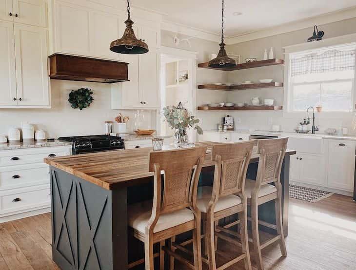 Counter height bar stools on dark kitchen island in white farmhouse kitchen