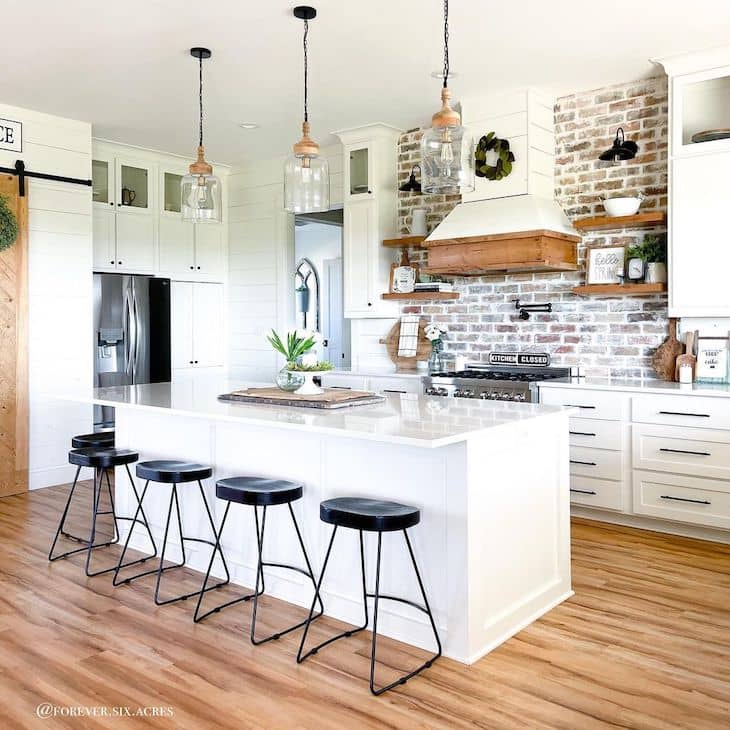No back bar stools in white farmhouse kitchen with brick backsplash