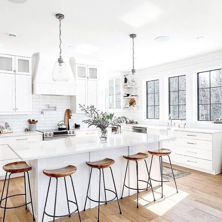 Wood bar stools with metal frame in a white farmhouse kitchen with wall of windows behind the kitchen sink