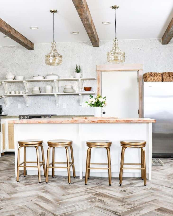 Brass bar stools in kitchen with open shelves and floor to ceiling Carrara marble backsplash