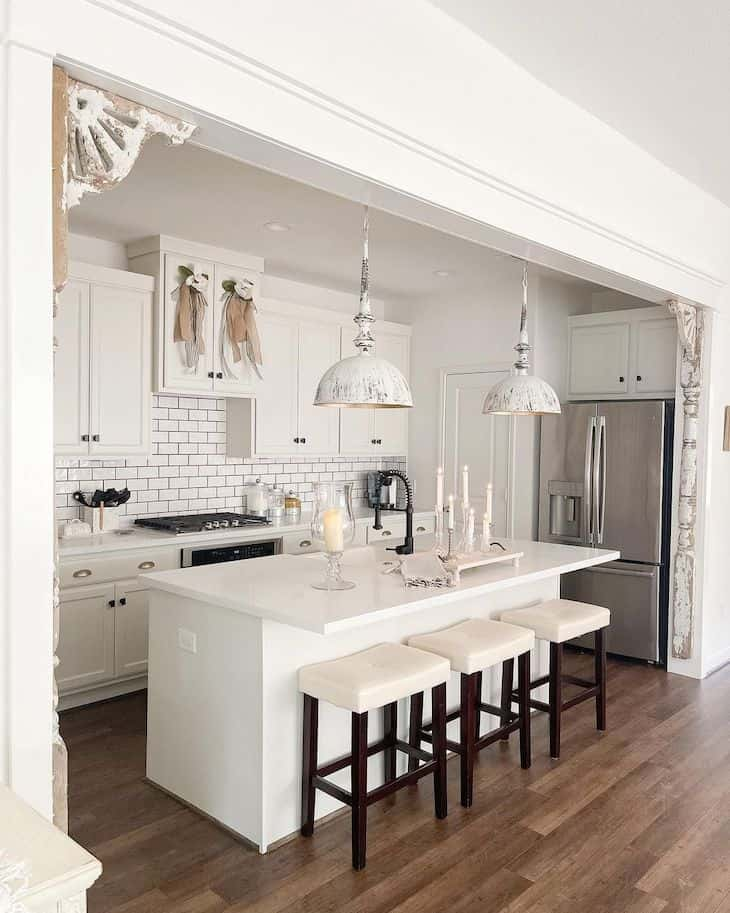 White kitchen with no back bar sools with dark wood legs and white upholstered seat