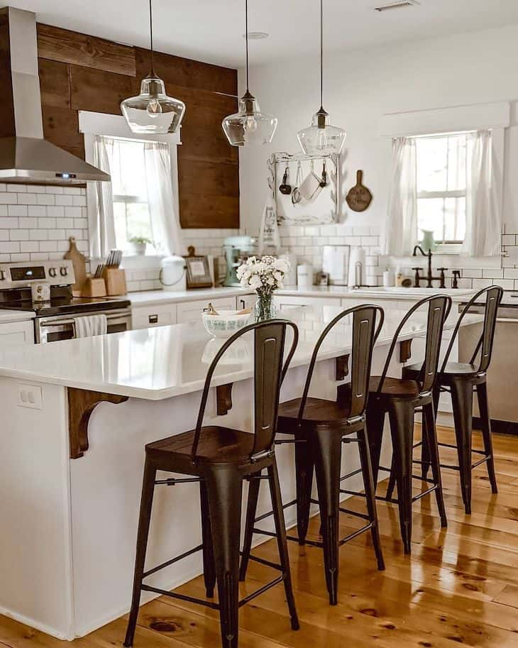 White rustic kitchen with no upper cabinets and black metal bar stools