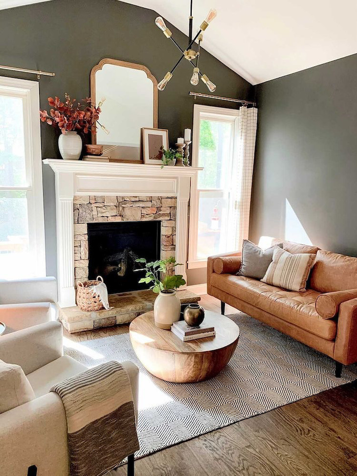 Brown leather couch in a living room with dark walls painted in Urban Bronze by Sherwin Williams
