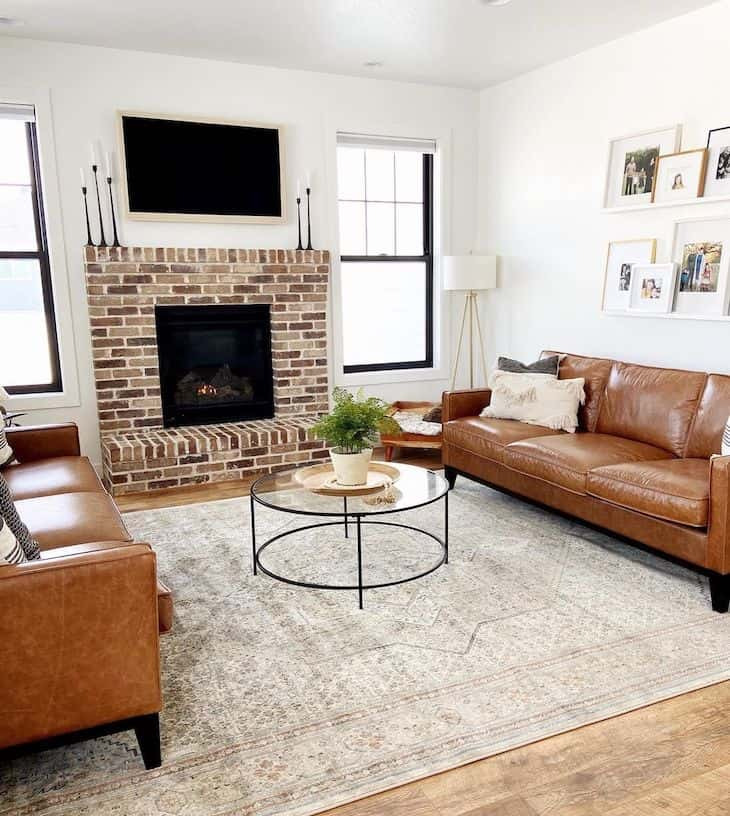 Farmhouse living room with brick fireplace and two brown sofas