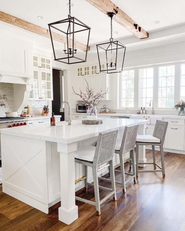 White kitchen island with three bar stools
