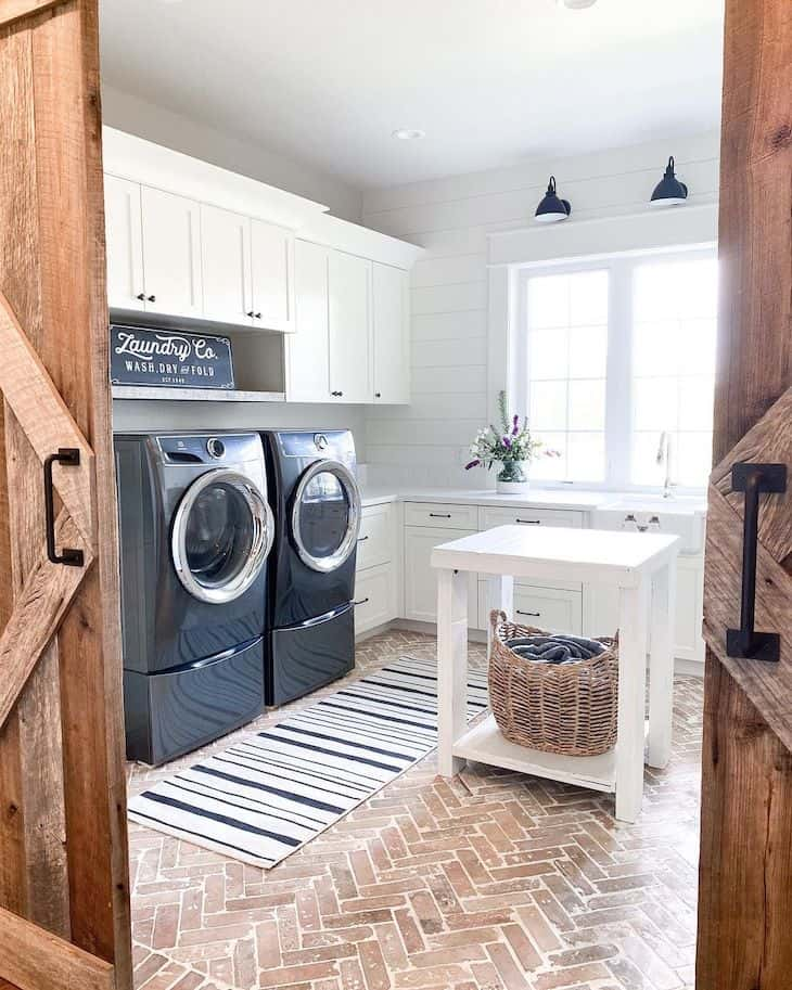 Large laundry room with black washer and dryer and brick floors