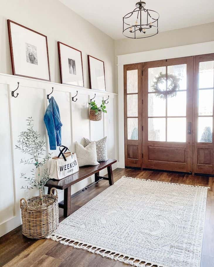 Entry way decor with a wooden bench and half board and batten wall