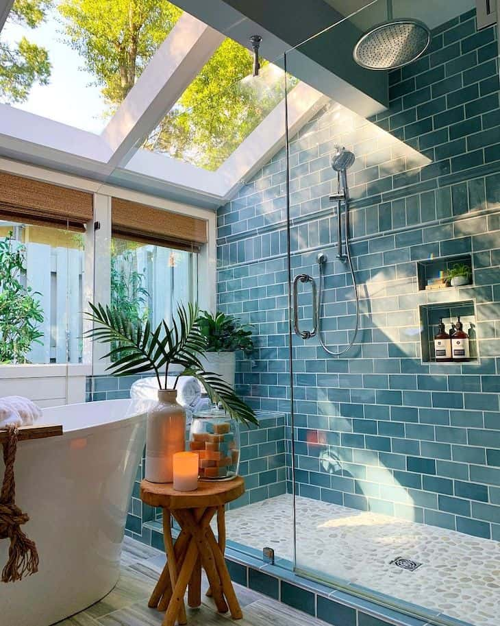 Turquoise shower tile and pebble shower floor tile in a coastal bathroom
