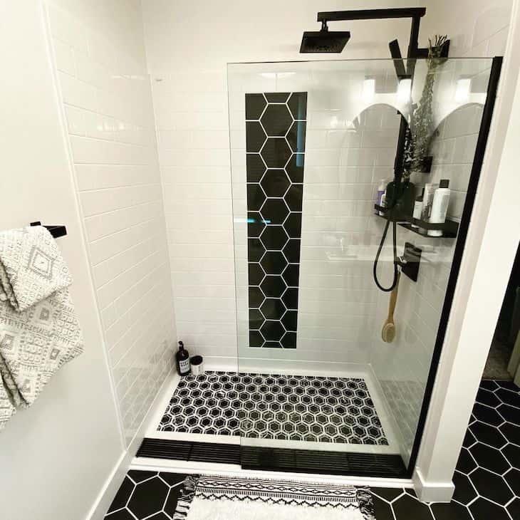 White shower tile in subway pattern with black floor tile