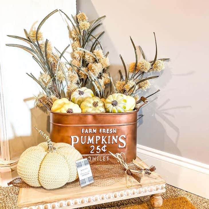 Copper bucket filled with pumpkins and dried stems on a wooden tray