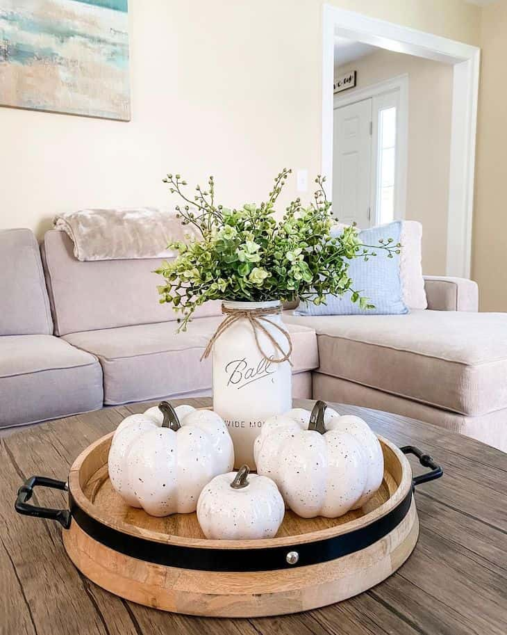 Fall coffee table decor with wooden tray filled with pumpkins and mason jar as vase