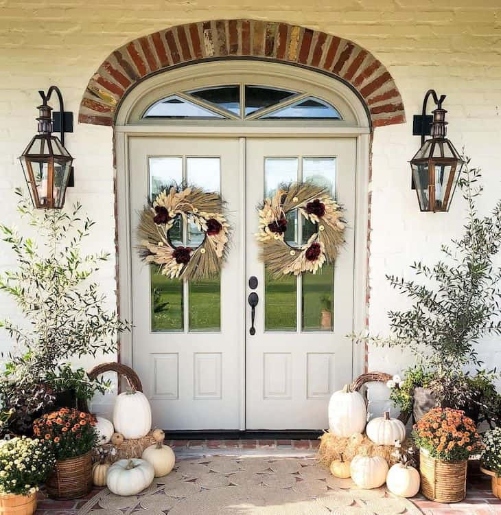 Double front door fall decor with two wreaths and pumpkins